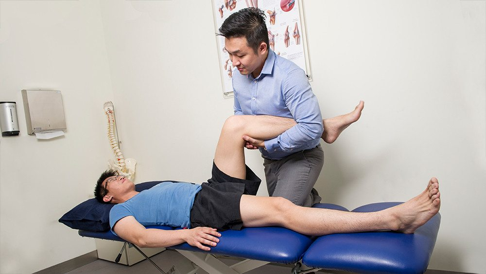 Physiotherapist assessing knee function of a patient