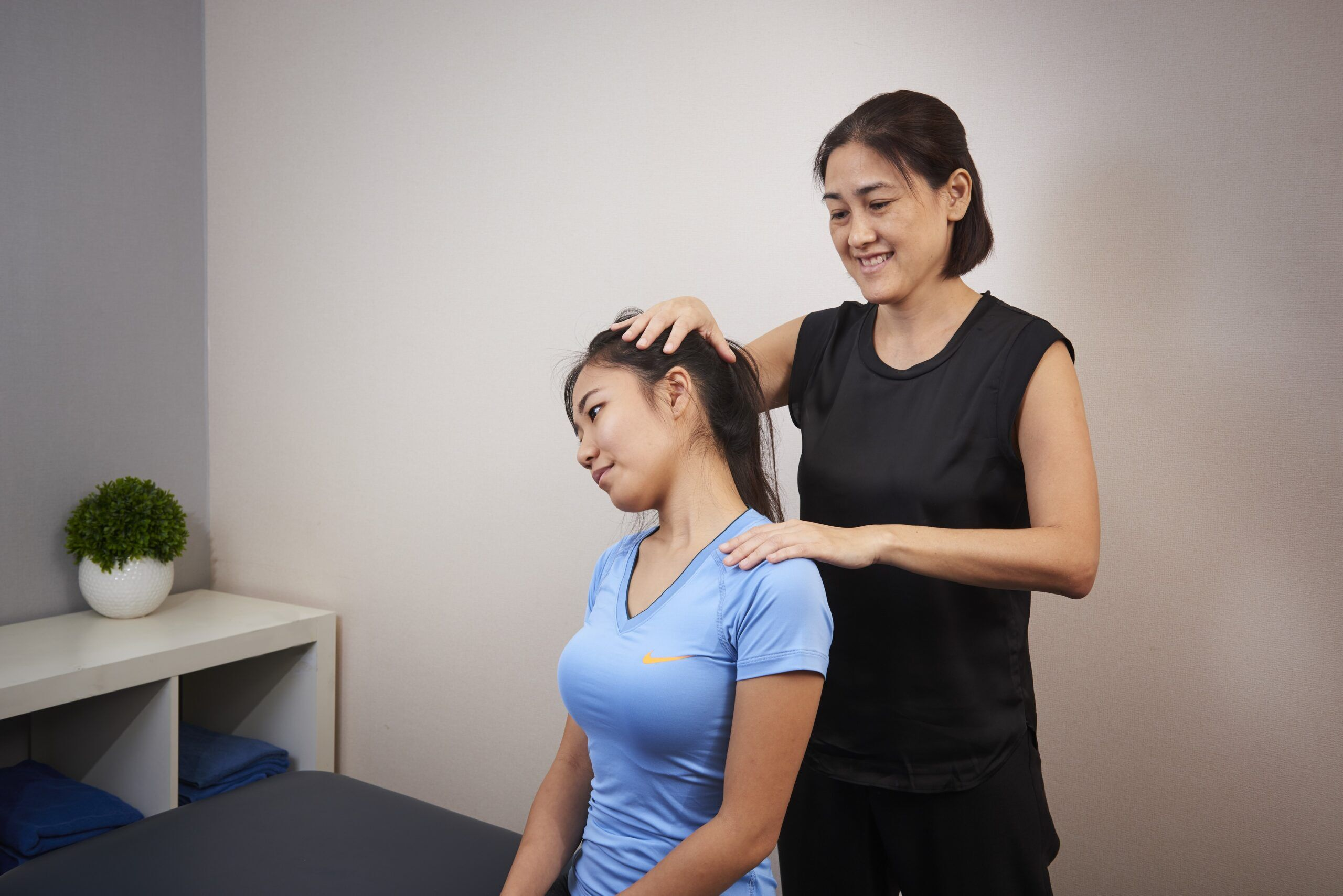 Physio giving client a neck assessment
