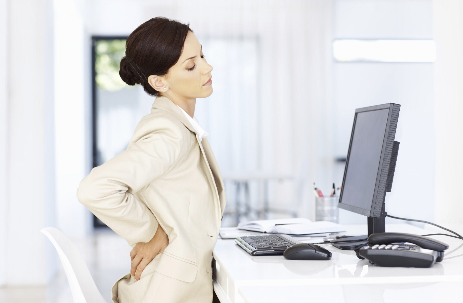 Lady in office looking at computer having back pain